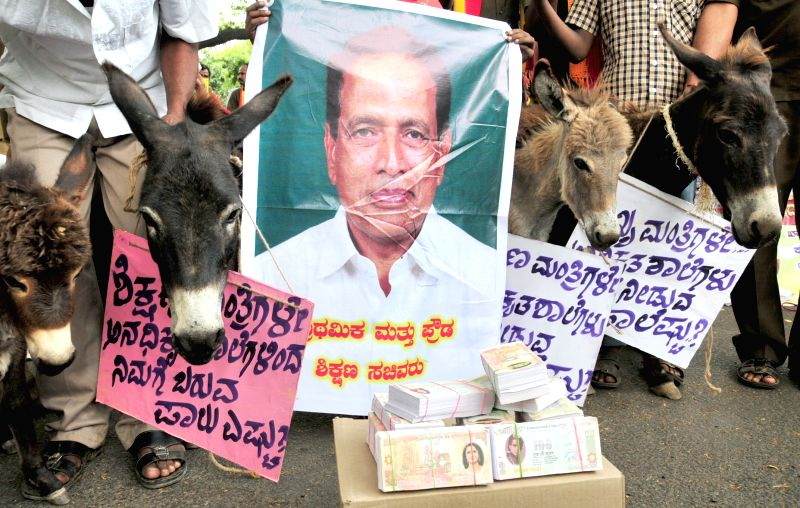 The members of Karnataka State Students Parents Forum stage a demonstration against state Education Minister Kimmane Ratnakar in Bengaluru, on March 31, 2015. - Kimmane Ratnakar