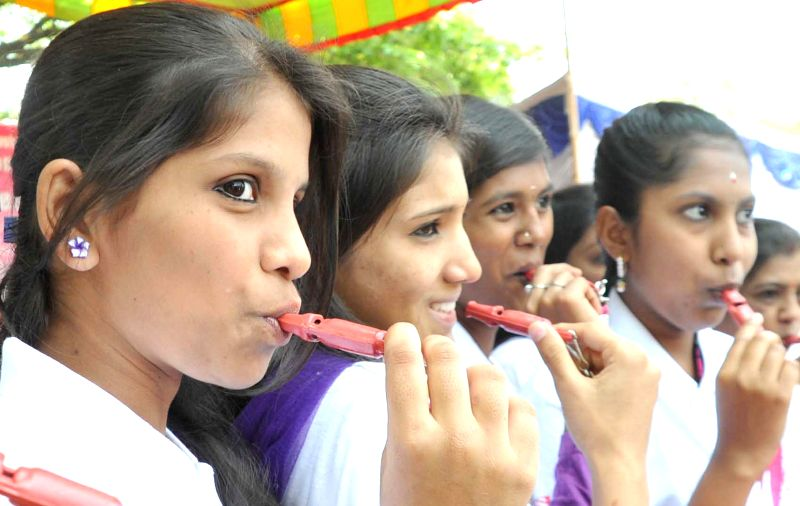 Volunteers of the Pink Whistle campaign distribute whistles to women on the International Day for Women in Bengaluru, on March 8, 2015.