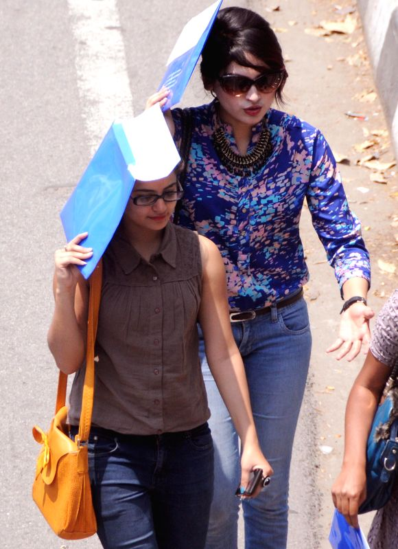 Women cover their faces as they walk in scorching sun in Bengaluru on March 24, 2015.