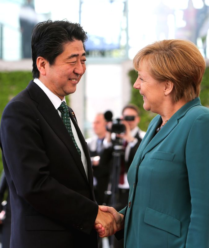 German Chancellor Angela Merkel (R) shakes hands with visiting Japanese Prime Minister Shinzo Abe during the welcoming ceremony at the Chancellery in Berlin, ...