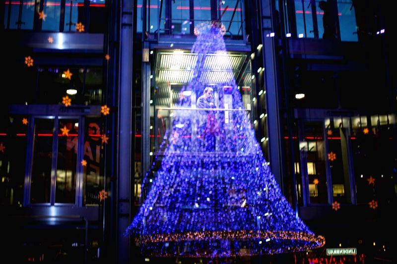 A man rides an elevator inside a building as Christmas light decorations are reflected on the glass in Berlin, Germany, on Dec, 23, 2014. (Xinhua/Zhang Fan) ...