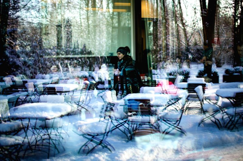 A woman walks through a coffee shop as snow-coverd tables and chairs are reflected on the window near Berlin's Tiergarten Park, in Berlin, Germany, on Dec. 29, 2014.