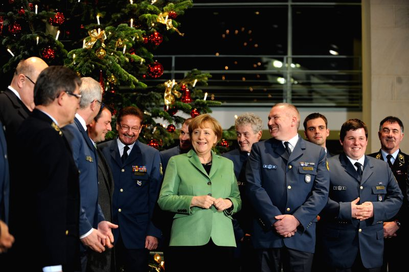 Berlin (Germany): German Chancellor Angela Merkel (C) stands in front of a Christmas tree in the chancellery in Berlin, Germany, Nov. 25, 2014. Merkel and her chief of staff Peter Altmaier attended ..