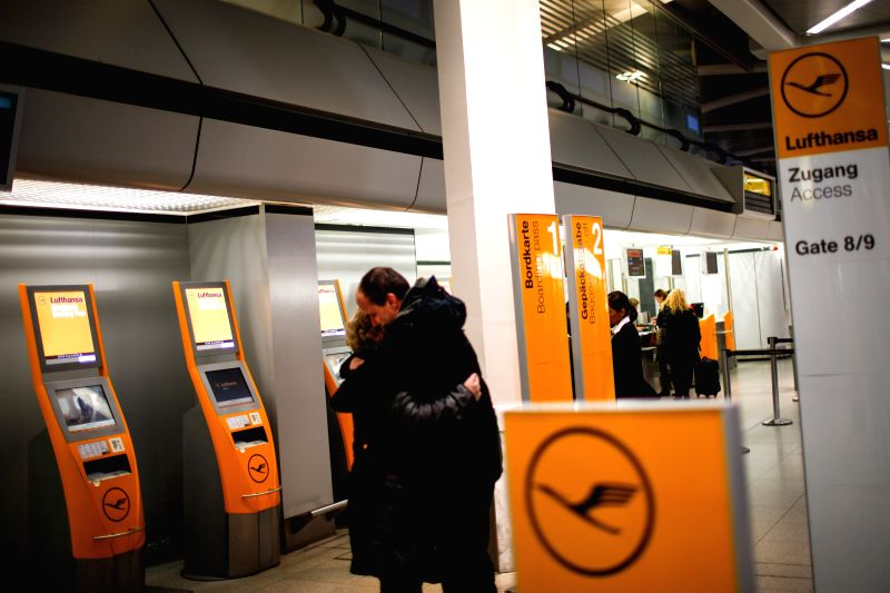 Berlin (Germany): Two passengers hold each other near Lufthansa's check-in desks in Tegel airport, Berlin, Germany, on Dec. 1, 2014.  German airline Lufthansa said on Monday that it had canceled ...