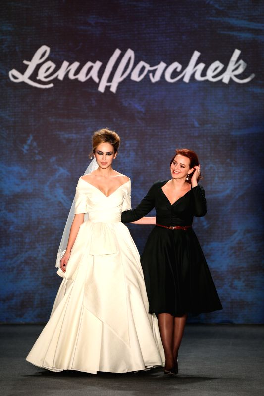 Austrian designer Lena Hoschek (R) greets the audience during the Mercedes-Benz Fashion Week Berlin Autumn/Winter 2015 in Berlin, Germany on Jan. 20, 2015. ...