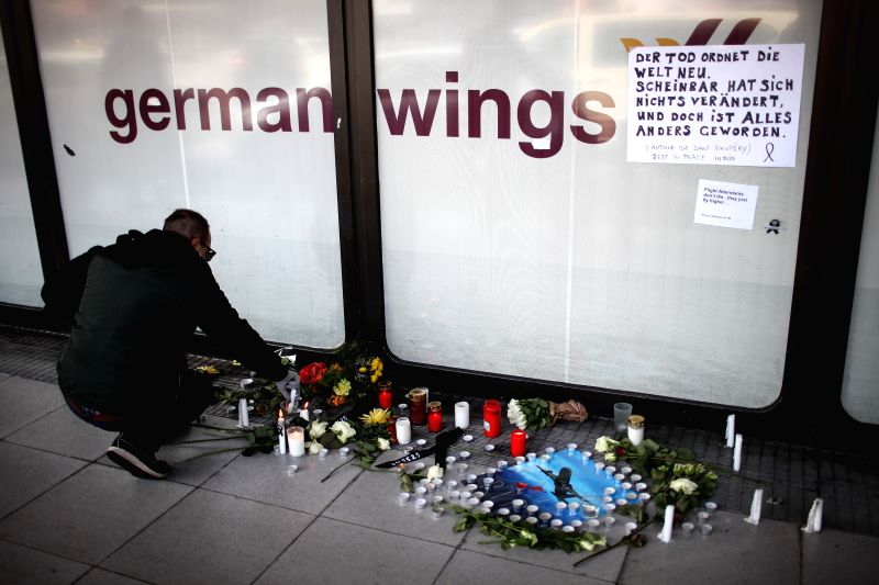 A man lights up candles to mourn victims of the crashed plane of Germanwings at the Tegel airport in Berlin, Germany, on March 25, 2015. An Airbus A320 of the ...
