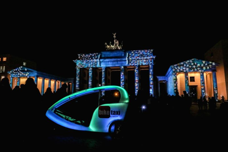 BERLIN, Oct. 6, 2017 - A tricycle with lights is seen in front of the illuminated Brandenburg Gate during the Festival of Lights in Berlin, capital of Germany, on Oct. 6, 2017. Berlin turned into a ...
