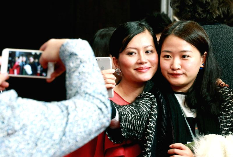 """Actress Do Thi Hai Yen (L) of film """"Big Father, Small Father and Other Stories"""" poses for photos with a fan during a press conference at the 65th ..."""
