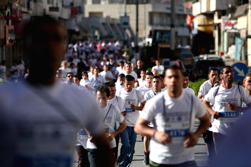 Participants run next to the controversial Israeli barrier during the second Palestine International Marathon in the West Bank city of Bethlehem on April 11, ...