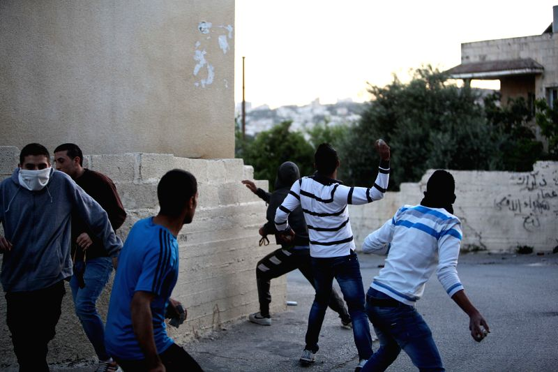 Palestinians throw stones at Israeli soldiers during a protest at the Aida refugee camp in the West Bank city of Bethlehem on April 14, 2014. (Xinhua/ Luay ...