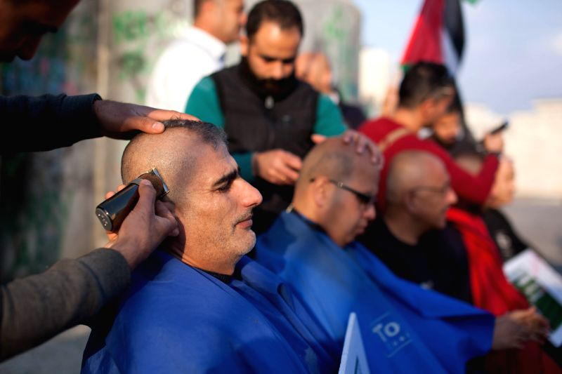 BETHLEHEM, April 17, 2017 - Palestinian protesters shave their heads in front of the separation wall during a demonstration supporting Palestinian prisoners in the West Bank city of Bethlehem, on ...
