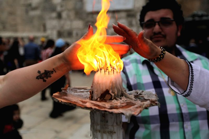Christian pilgrims touch the Holy Fire at the Church of the Nativity in the West Bank city of Bethlehem, April 19, 2014. During the annual ceremony, top clerics .