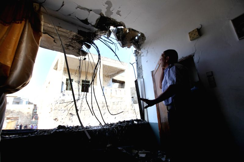 A Palestinian looks at a damaged building hit by a rocket believed to be fired by Palestinian militants from the Gaza Strip, in the West Bank town of Beit Sahour ..