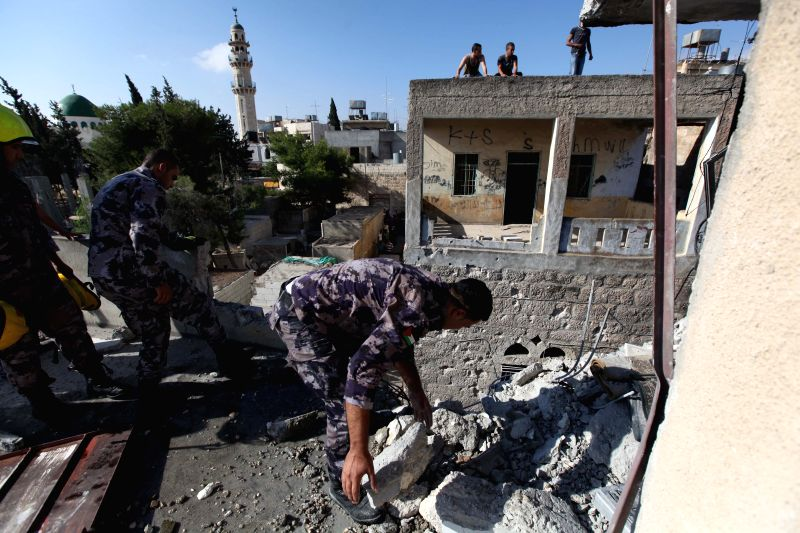 Palestinians inspect a damaged building hit by a rocket believed to be fired by Palestinian militants from the Gaza Strip, in the West Bank town of Beit Sahour ...