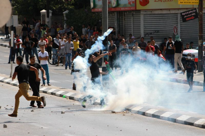 A Palestinian protester throws a gas canister fired by Israeli soldiers during clashes following a demonstration against the Israeli offensive in Gaza, in the ..
