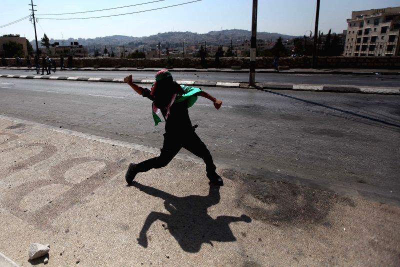 A Palestinian protester throws stones at Israeli soldiers during clashes following a demonstration against the Israeli offensive in Gaza, in the West Bank city .