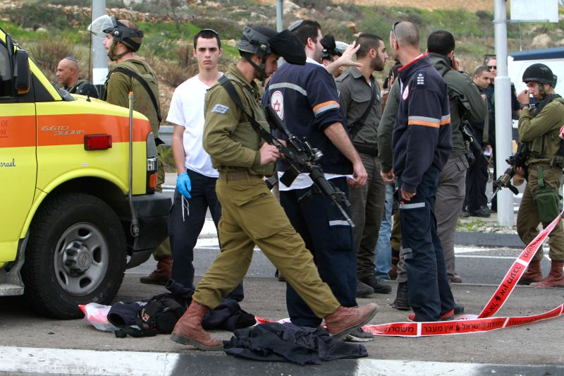 Israeli security forces inspect the scene of an acid attack by a Palestinian near a checkpoint outside the West Bank city of Bethlehem, on Dec. 12, 2014. A ...