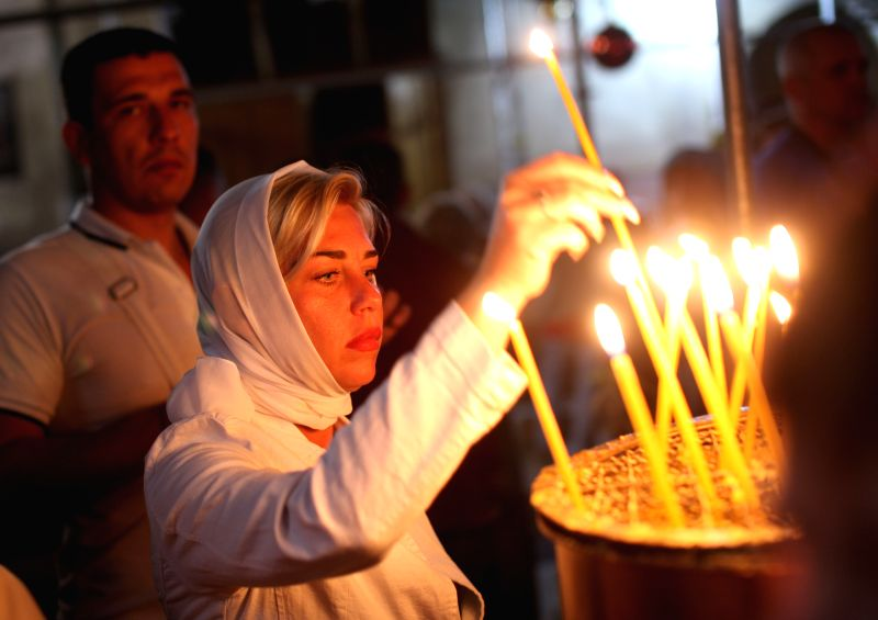 A Christian worshiper lights candles during the last Sunday Mass before Christmas at the Church of the Nativity, in the West Bank city of Bethlehem, Dec. 21, 2014.