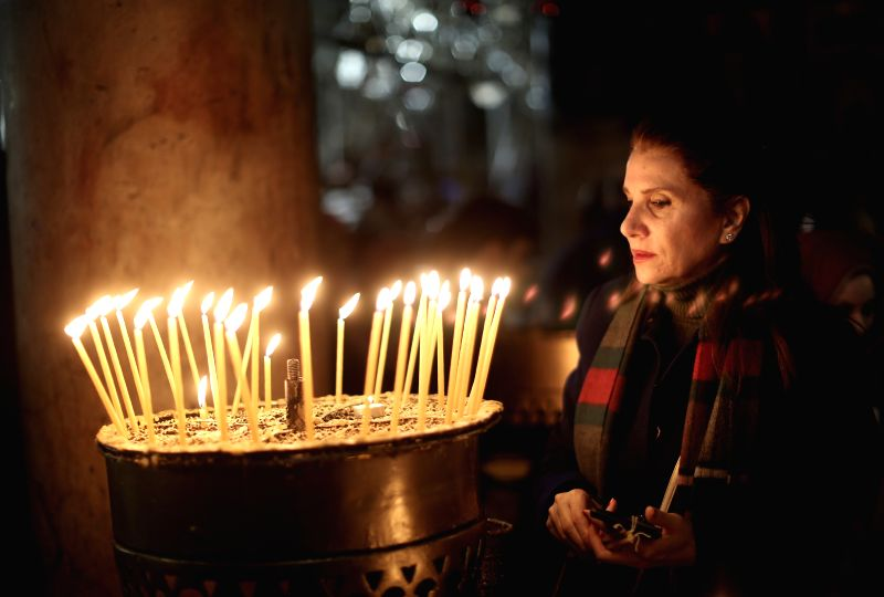 A Palestinian Worshiper prays in front of candles inside the Church of the Nativity in the West Bank city of Bethlehem on Dec. 24, 2014. Thousands of Christian ...