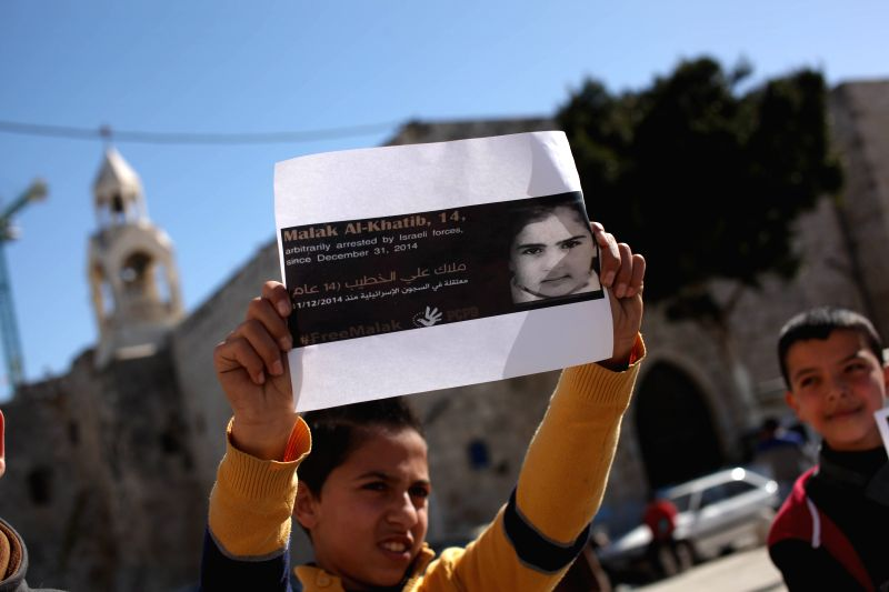 A Palestinian boy holds a poster of 14-year-old Malak al-Khatib during a protest against the arrest of al-Khatib, calling for her release in front of the Church ..