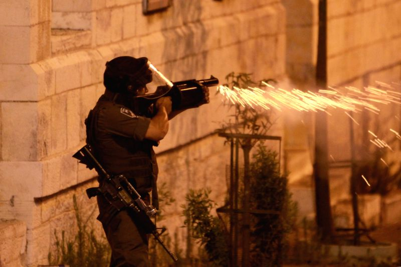 An Israeli soldier shoots during clashes with Palestinian citizens near an Israeli checkpoint in the West Bank city of Bethlehem, on July 10, 2014. (Xinhua/ Luay .