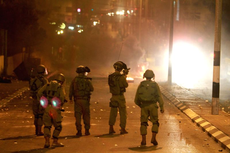 Israeli soldiers shoot during clashes with Palestinian citizens near an Israeli checkpoint in the West Bank city of Bethlehem, on July 10, 2014. (Xinhua/ Luay ...