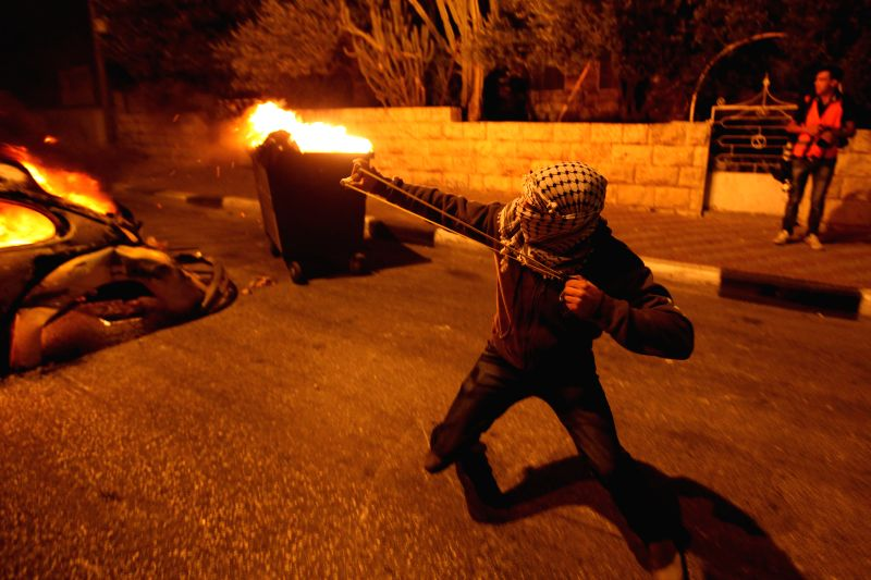 A Palestinian protestor uses a sling to throw a stone at Israeli soldiers during clashes in the West Bank city of Bethlehem on July 22, 2014.