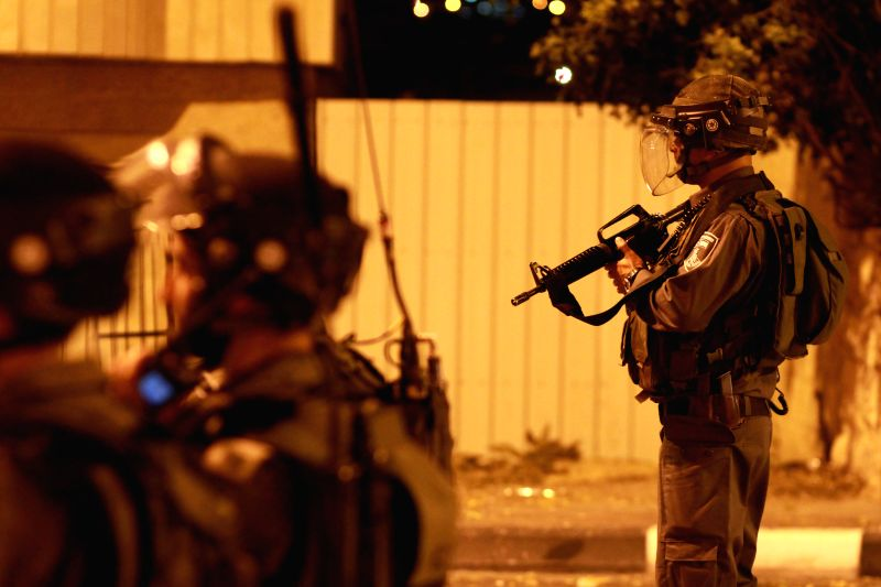 Israeli soldiers take positions during clashes with Palestinian youths near Rachel's Tomb in the West Bank city of Bethlehem, on July 2, 2014. The discovery of a ..
