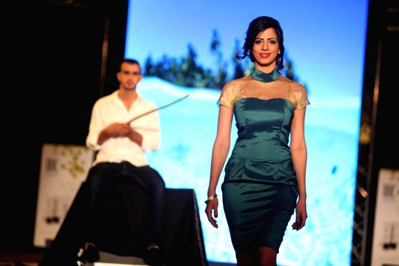 A Palestinian model displays a dress during a fashion show in the West Bank city of Bethlehem, on June 25, 2014.