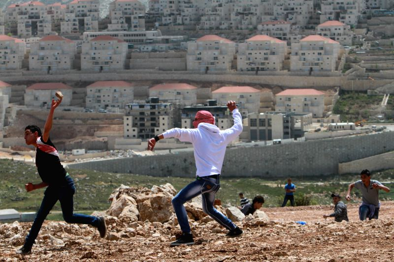 Palestinian protesters hurl stones toward Israeli soldiers during a protest marking Land Day, in Wadi Fukin village near the West Bank City of Bethlehem on ...