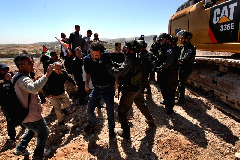 A Palestinian protester scuffles with Israeli soldiers during a protest against the confiscation of the land by Israel for Jewish settlements near the West Bank ...