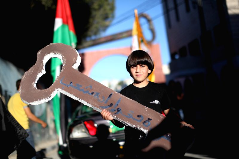 A Palestinian child takes part in a rally ahead of the 66th anniversary of Nakba at Aida refugee camp in the West Bank city of Bethlehem, on May 14, 2014. ...