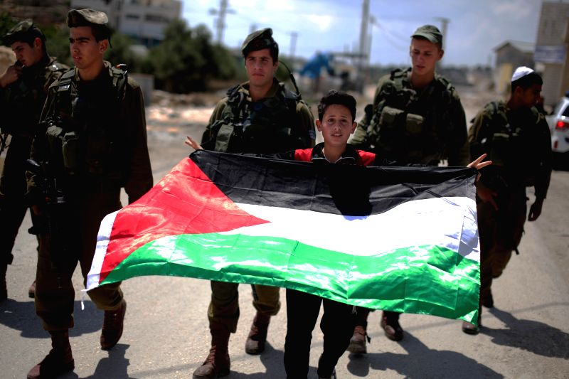 A Palestinian boy waves a flag as he takes part in a protest against Israel's controversial separation barrier in Al-Maasarah village near the West Bank city of ...