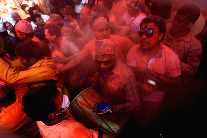 "Nepaleses throw vermilion powder during the traditional ""Sindoor Jatra"" festival at Thimi, Bhaktapur, Nepal, April 15, 2014. The festival is celebrated"