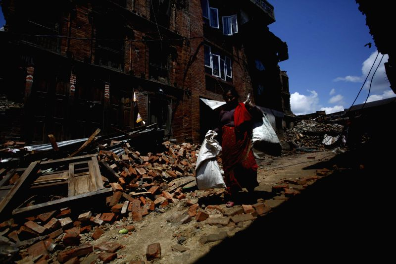 A woman collects her belongings from houses damaged by earthquake in Bhaktapur, Nepal, April 27, 2015. Death toll climbed to 3,815 following a massive ...