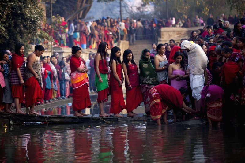 Nepalese Hindu devotees pray at the Hanumante River during the last day of Madhav Narayan festival in Bhaktapur, Nepal, on Feb. 3, 2015. During the month-long ...