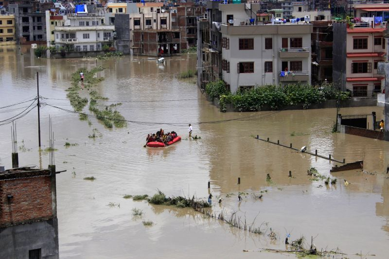 BHAKTAPUR, July 12, 2018 - Nepalese residents sit in a lifesaving raft in Bhaktapur, Nepal, July 12, 2018. Many areas in Nepal were inundated due to the swollen river following torrential rains on ...
