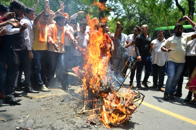 Bharatiya Janata Yuva Morcha (BJYM) activists stage a demonstration against public slaughter of an ox - as part of protests against new cattle slaughter rules by Youth Congress activists ...