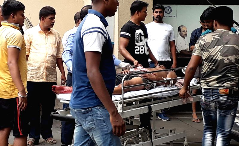 Bhatpara: One of the persons who sustained injuries during violence that erupted at Bhatpara in West Bengal's North 24 Parganas district, being taken for treatment on June 20, 2019. One person was killed in the incident. Prior to the inauguration of