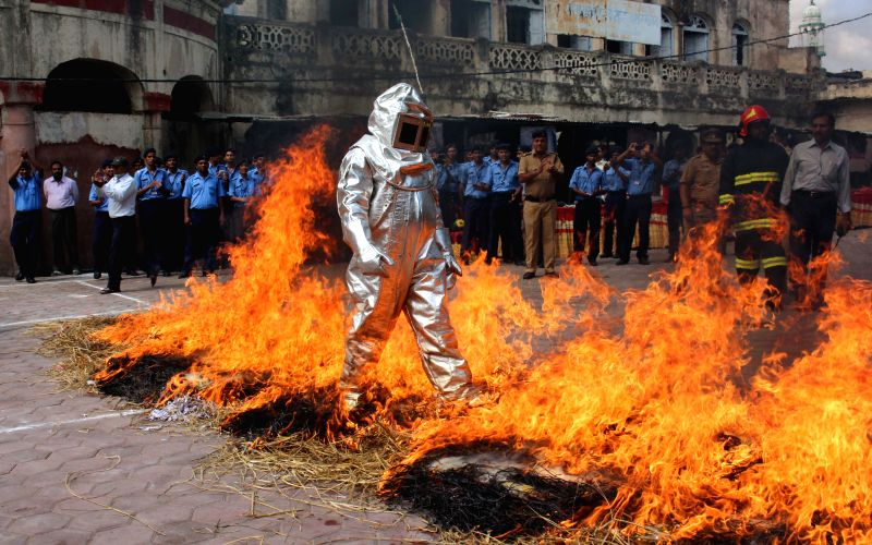 A fire fighter walks on burning hay during a programme organised on National Fire Service Day in Bhopal, on April 14, 2015.