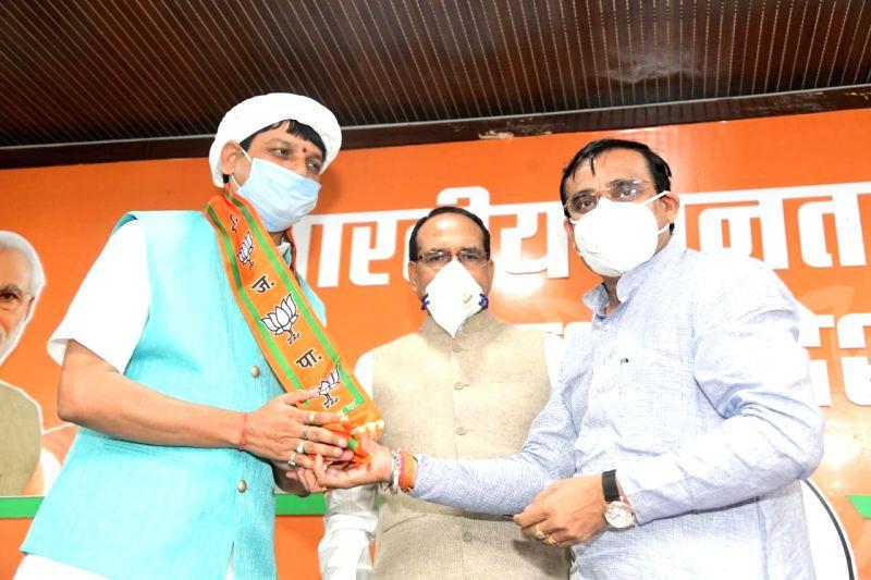 Bhopal: Congress MLA from Bada Malahara Assembly segment, Praduman Lodhi joins the BJP in the presence of Madhya Pradesh Chief Minister Shivraj Singh Chouhan and state BJP chief VD Sharma, in Bhopal on July 12, 2020. (Photo: IANS)