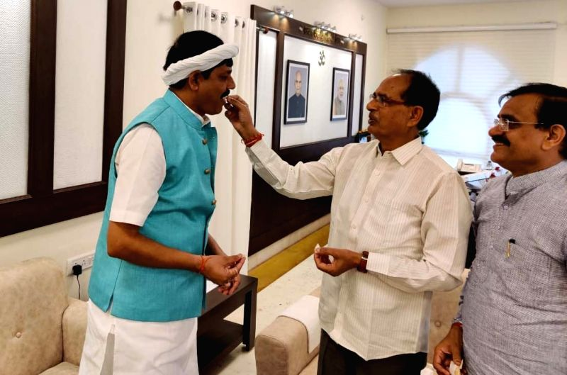 Bhopal: Former Congress MLA from Bada Malahara Assembly segment, Praduman Lodhi being offered sweets by Madhya Pradesh Chief Minister Shivraj Singh Chouhan during the former's visit to Chouhan's residence after joining the BJP, in Bhopal on July 12,