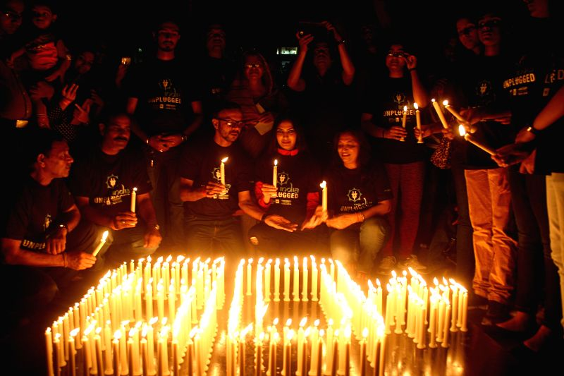 Parul Mishra, Miss Asia Pacific 2011 and others light up candles during Earth Hour celebration in Bhopal on March 28, 2015. - Parul Mishra