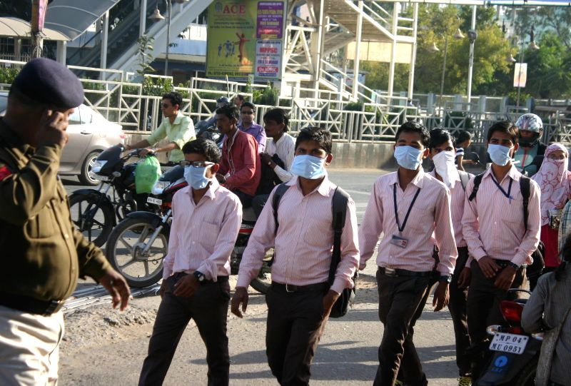 People wear masks as a protective measure against swine flu in Bhopal on Feb 18, 2015.