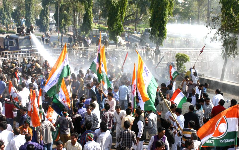 Policemen charge water cannons on Congress workers demonstrating against the Congress workers protesting against the Vyapam scam in Bhopal, on Feb 18, 2015.