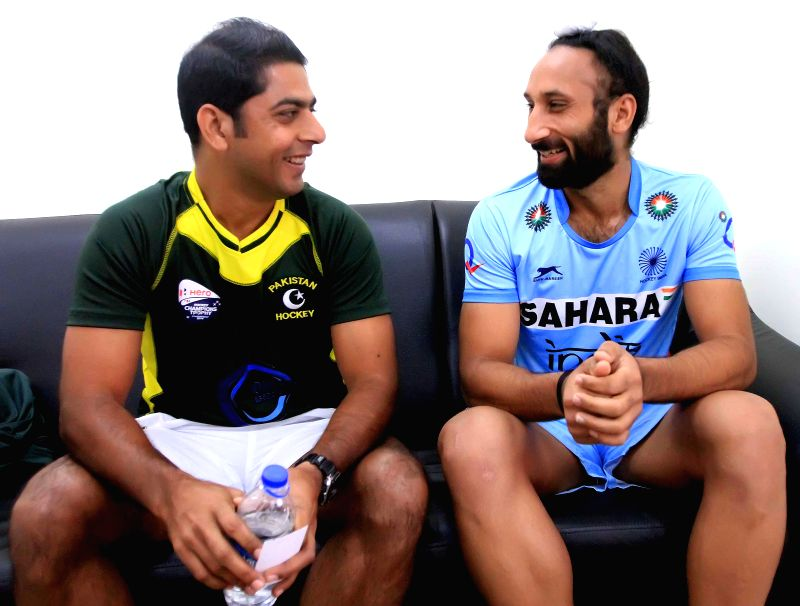 Indian Hockey team captain Sardar Singh and Pakistan Hockey team captain Muhammad Imran share a light moment after unveiling the trophy of Hero Men's Champions Trophy 2014 in ...