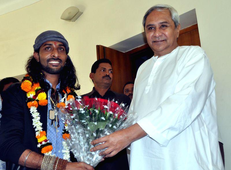 Odisha Chief Minister Naveen Patnaik greets India's Raw Star winner Rituraj Mohanty in Bhubaneswar, on Dec 14, 2014. (Photo : Arabinda Mahapatra/IANS) - Naveen Patnaik