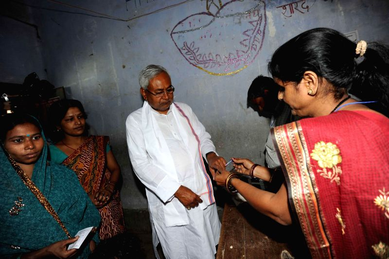 Bihar Chief Minister Nitish Kumar gets his forefinger marked with phosphoric ink after casting his vote during the fifth phase of 2014 Lok Sabha Polls in Patna on April 17, 2014.