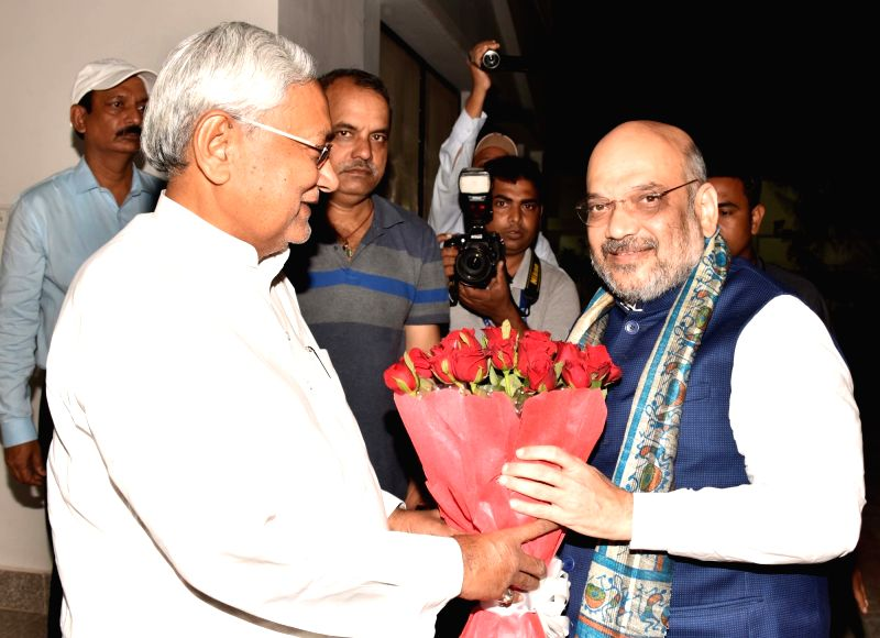 Bihar Chief Minister Nitish Kumar greets BJP Chief Amit Shah during a dinner party at his official residence in Patna on July 12, 2018. - Nitish Kumar and Amit Shah
