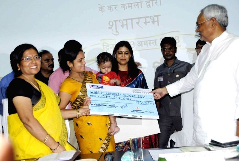 "Bihar Chief Minister Nitish Kumar hands over a cheque of Rs 2,000 to beneficiaries of ""Mukhyamantri Kanya Utthan Yojana"", in Patna, on  Aug 3, 2018 - Nitish Kumar"